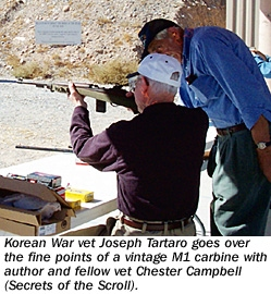 Korean War vet Joseph Tartaro goes over the fine points of a vintage M1 carbine with author and fellow vet Chester Campbell (Secrets of the Scroll)
